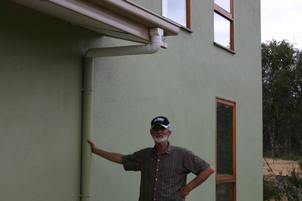 Lee Hunter outside his straw panel and internal mud brick wall house.