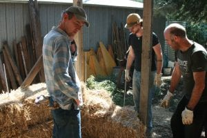 Joel Meadows (right) positions straw bales with help from friends Sid Larwil (left) and Brad Welsh.
